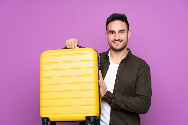 Hombre guapo joven sobre pared púrpura aislada en vacaciones con maleta de viaje