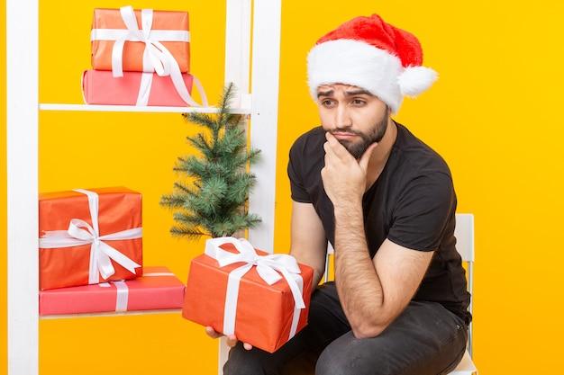 Hombre guapo joven con un sombrero de santa claus está sosteniendo regalos de felicitación junto a un árbol de navidad. concepto de vacaciones de navidad y año nuevo.