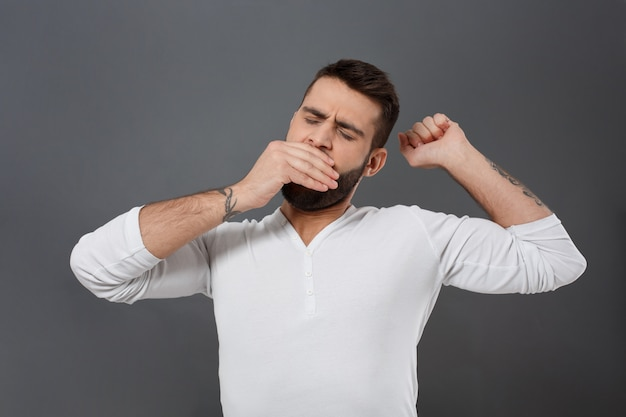 Hombre guapo joven soñoliento bostezando sobre pared gris