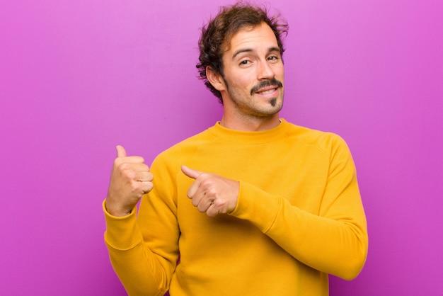 Hombre guapo joven sonriendo alegremente y casualmente apuntando a copiar espacio en el costado, sintiéndose feliz y satisfecho sobre la pared púrpura