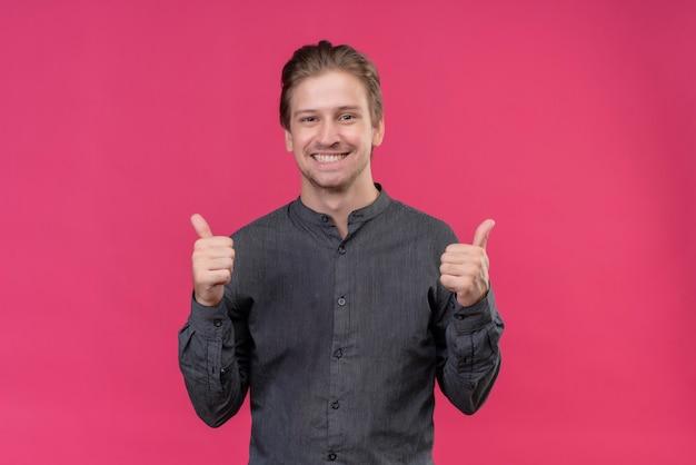Hombre guapo joven sonriendo alegremente mostrando los pulgares para arriba de pie sobre la pared rosa