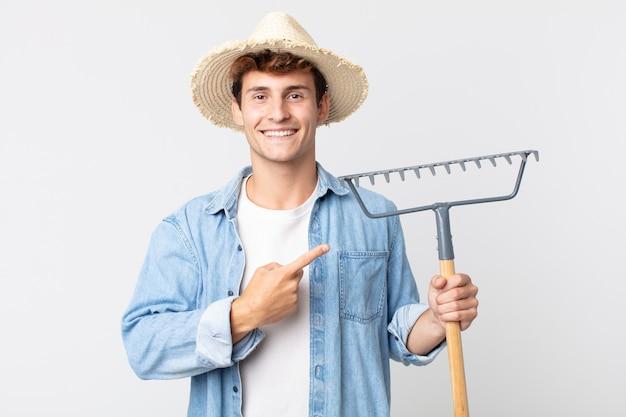 Hombre guapo joven sonriendo alegremente, sintiéndose feliz y apuntando hacia un lado. concepto de granjero