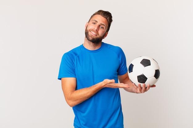 Hombre guapo joven sonriendo alegremente, sintiéndose feliz y mostrando un concepto