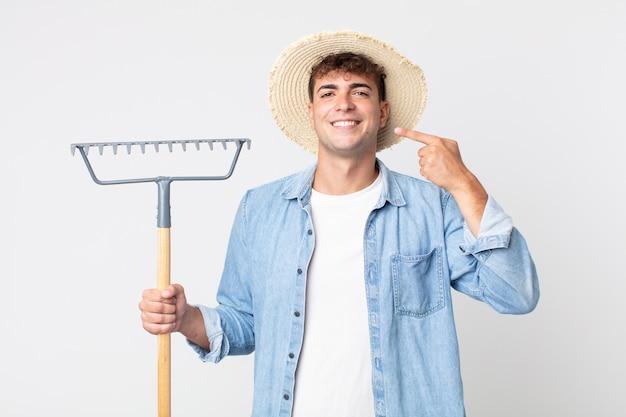 Hombre guapo joven sonriendo con confianza apuntando a su propia amplia sonrisa. concepto de granjero