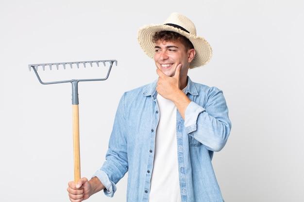 Hombre guapo joven sonriendo con una expresión feliz y segura con la mano en la barbilla. concepto de granjero