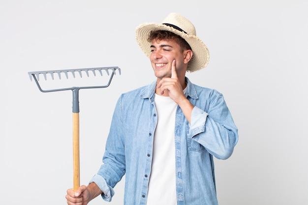 Hombre guapo joven sonriendo felizmente y soñando despierto o dudando. concepto de granjero