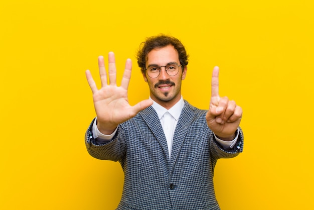 Hombre guapo joven sonriendo y mirando amigable, mostrando el número seis o sexto con la mano hacia adelante, contando contra naranja