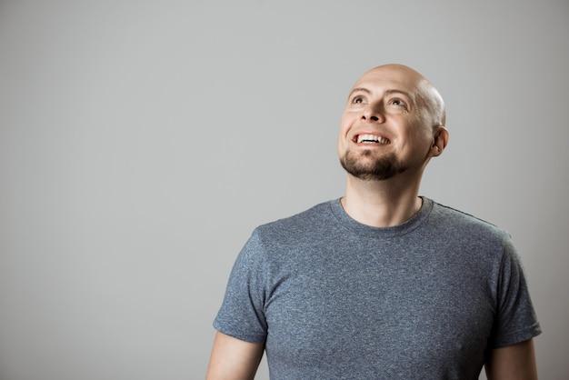 Hombre guapo joven sonriendo, mirando por encima de la pared de color beige