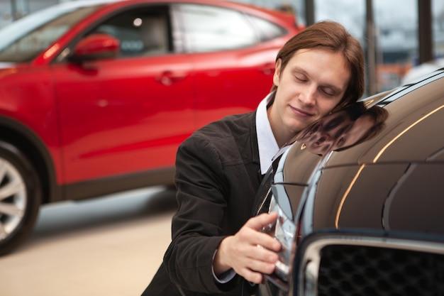 Hombre guapo joven sonriendo con los ojos cerrados, abrazando el coche nuevo en el concesionario