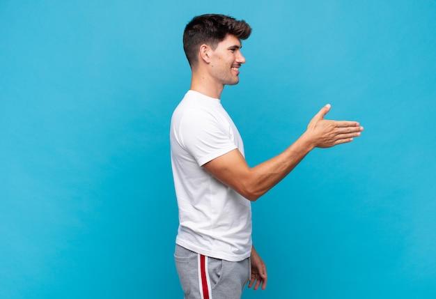 Hombre guapo joven sonriendo, saludándote y ofreciendo un apretón de manos para cerrar un trato exitoso, concepto de cooperación
