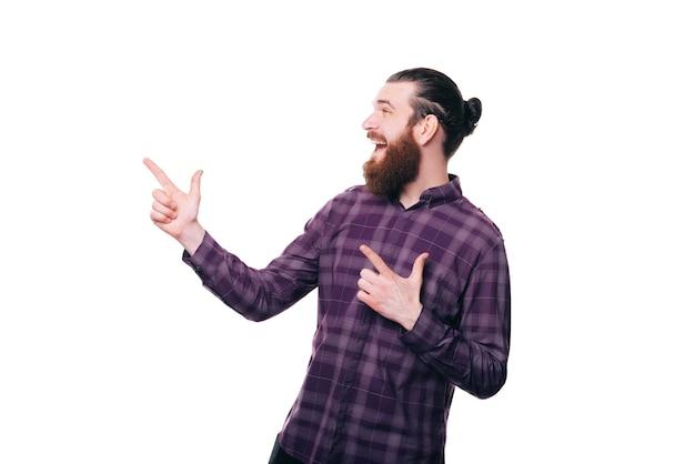 Hombre guapo joven sorprendido apuntando a la esquina sobre la pared blanca