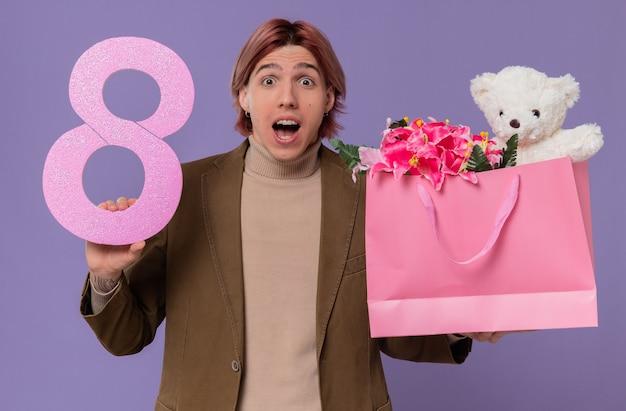 Hombre guapo joven sorprendido sosteniendo rosa número ocho y bolsa de regalo con flores y oso de peluche