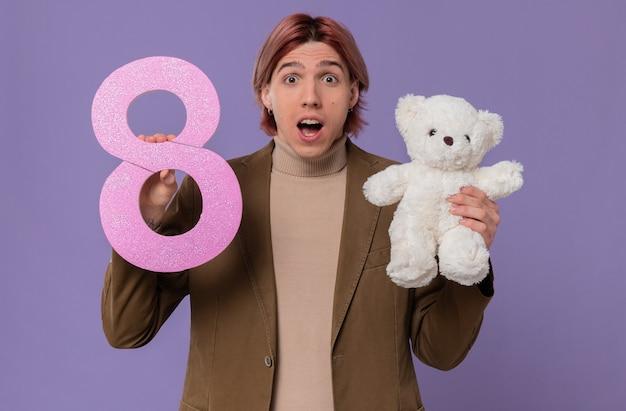 Hombre guapo joven sorprendido sosteniendo rosa número ocho y oso de peluche blanco