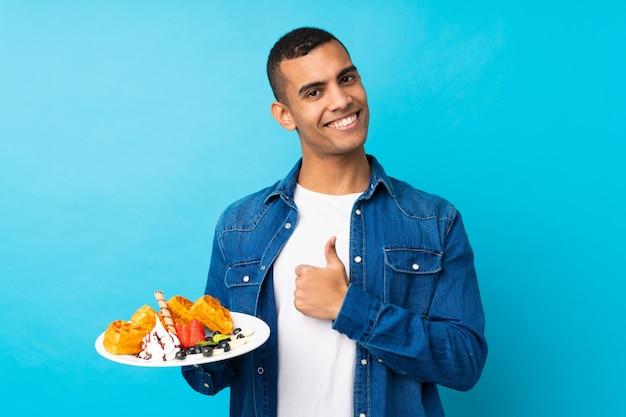 Hombre guapo joven sosteniendo gofres sobre pared azul aislada con los pulgares hacia arriba porque algo bueno ha sucedido