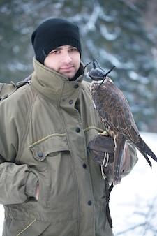 Hombre guapo joven sosteniendo un halcón en su brazo