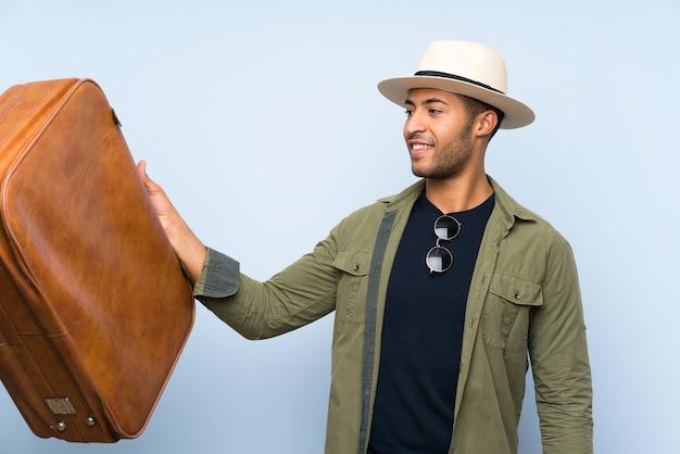 Hombre guapo joven sosteniendo un maletín vintage sobre pared azul aislada con expresión feliz