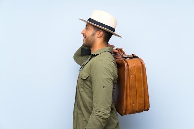 Hombre guapo joven sosteniendo un maletín vintage