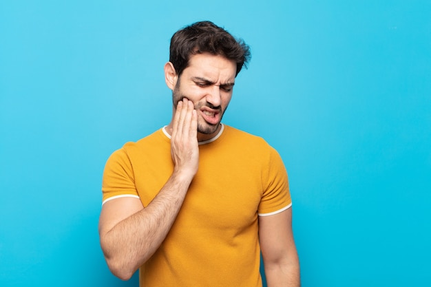 Hombre guapo joven sosteniendo la mejilla y sufriendo dolor de muelas, sintiéndose enfermo, miserable e infeliz, buscando un dentista