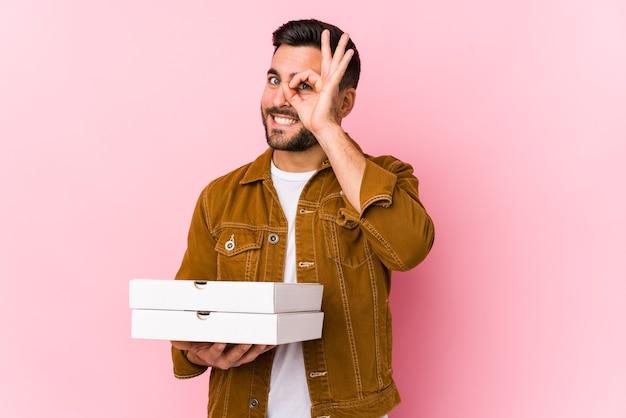 Hombre guapo joven sosteniendo pizzas aislado emocionado manteniendo el gesto ok en el ojo.