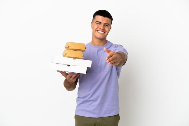 Hombre guapo joven sosteniendo pizzas y hamburguesas sobre fondo blanco aislado un apretón de manos para cerrar un buen trato