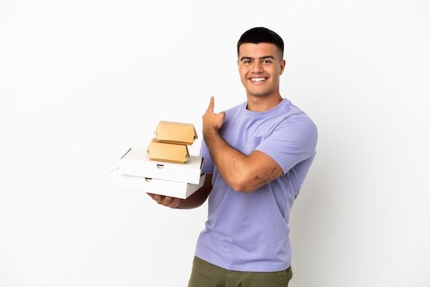Hombre guapo joven sosteniendo pizzas y hamburguesas sobre fondo blanco aislado apuntando hacia atrás