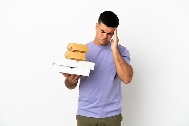 Hombre guapo joven sosteniendo pizzas y hamburguesas sobre fondo blanco aislado con dolor de cabeza