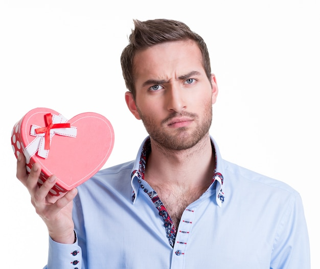 Hombre guapo joven sosteniendo un regalo y pensando - aislado en blanco