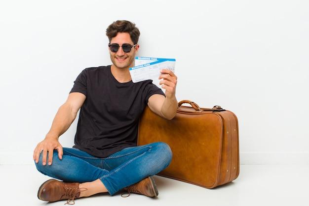 Hombre guapo joven con una tarjeta de embarque boletos sentados en el suelo en una habitación blanca