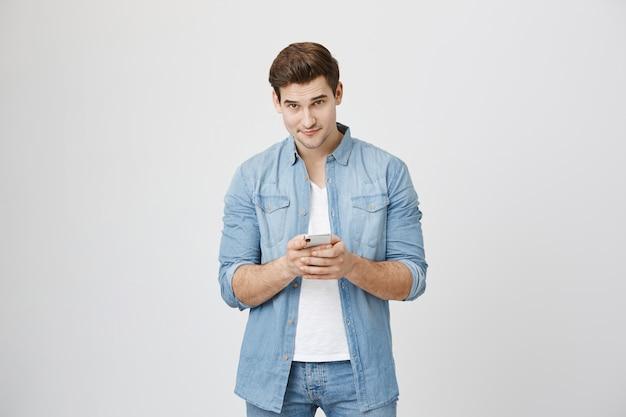 Hombre guapo joven con teléfono móvil, mirando