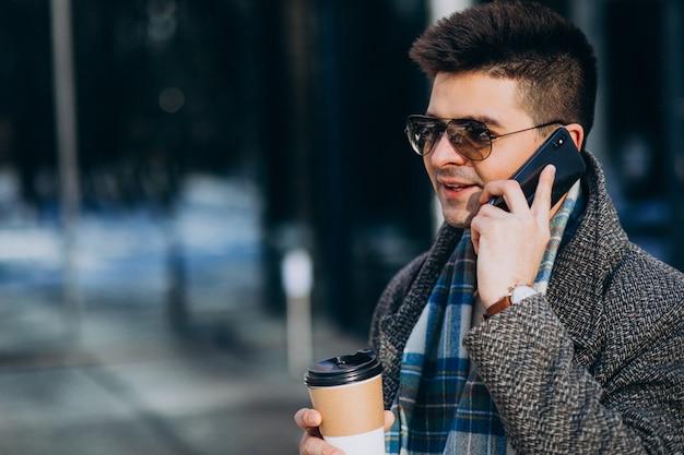 Hombre guapo joven tomando café fuera y usando el teléfono