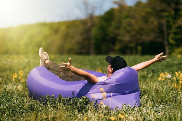 Hombre guapo joven tumbado en el sofá de aire lamzac, cerca del bosque