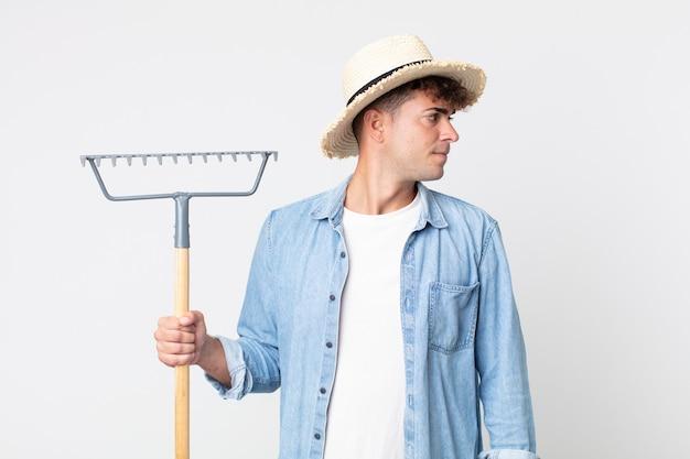 Hombre guapo joven en vista de perfil pensando, imaginando o soñando despierto. concepto de granjero