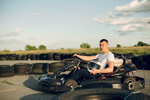 Hombre guapo en un karting con un auto