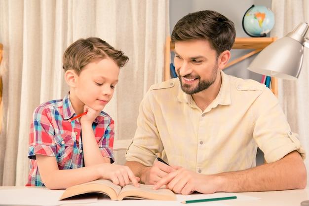 Hombre guapo leyendo cuento de hadas a su pequeño hijo