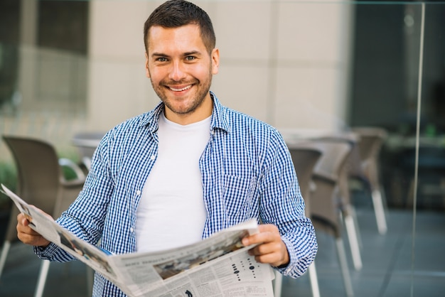 Hombre guapo leyendo periódico en café