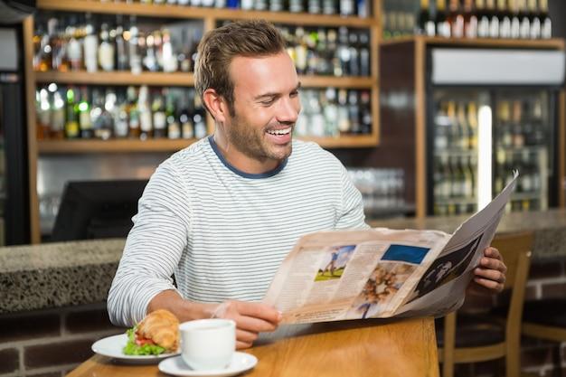 Hombre guapo leyendo el periódico y tomando un café