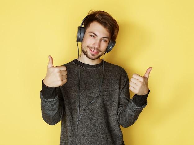 Hombre guapo licuando a la música sobre fondo amarillo