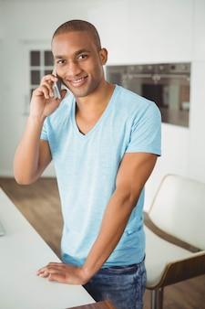 Hombre guapo en una llamada telefónica en la cocina
