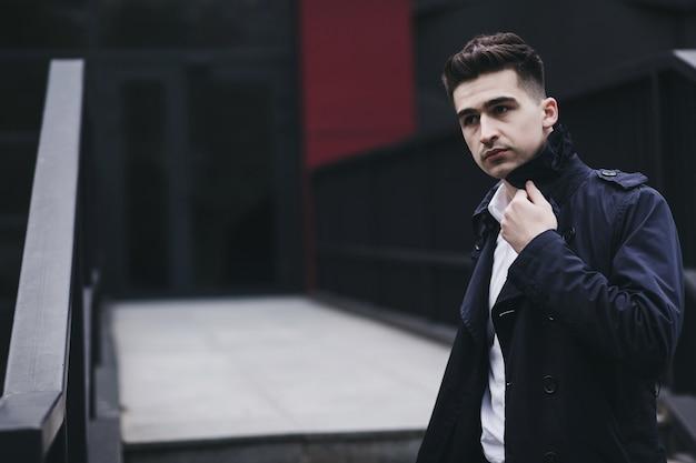 Hombre guapo lleva un abrigo y una camisa en la ciudad. colección otoño-primavera
