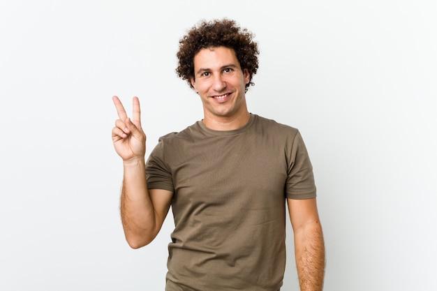 Hombre guapo maduro aislado alegre y despreocupado mostrando un símbolo de paz con los dedos.