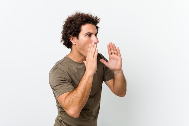 Hombre guapo maduro aislado grita fuerte, mantiene los ojos abiertos y las manos tensas.