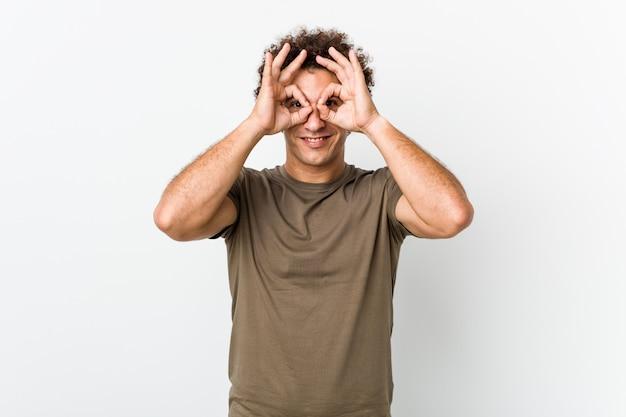 Hombre guapo maduro aislado mostrando bien firmar sobre los ojos