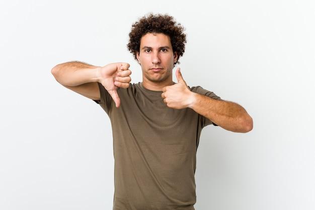 Hombre guapo maduro aislado mostrando los pulgares hacia arriba y hacia abajo, difícil elegir el concepto