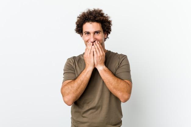 Hombre guapo maduro riéndose de algo, cubriendo la boca con las manos.