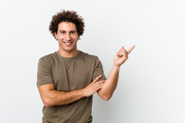 Hombre guapo maduro sonriendo alegremente señalando con el dedo lejos.