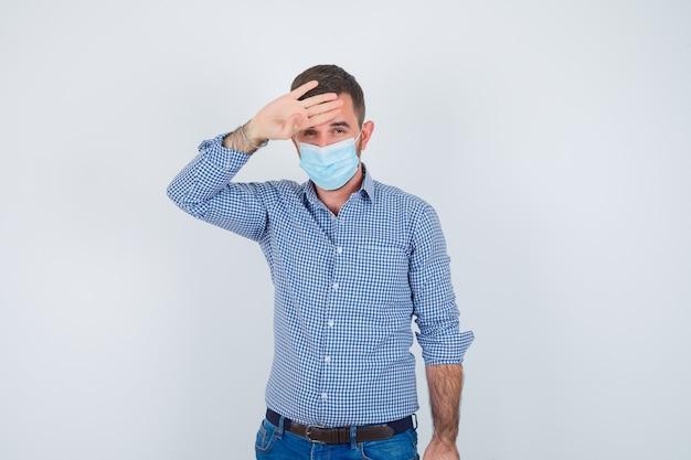 Hombre guapo con la mano en la cabeza, controlando su temperatura en camisa, jeans, máscara y luciendo exhausto. vista frontal.