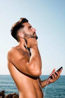 Hombre guapo mirando al cielo y escuchando música