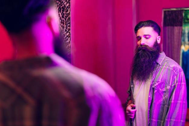 Hombre guapo mirando a sí mismo en el espejo con camisa nueva