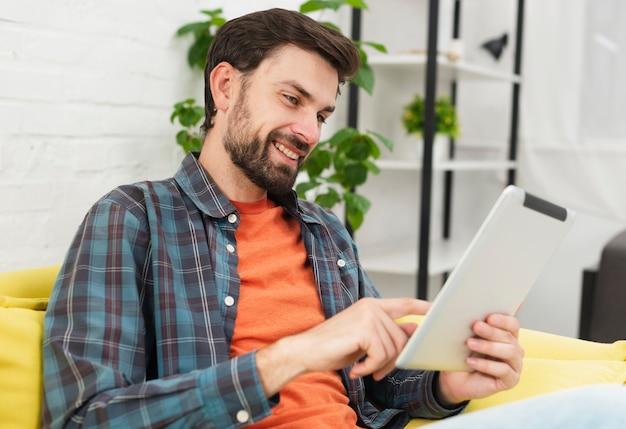 Hombre guapo mirando en tableta
