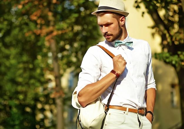 Hombre guapo modelo hipster en ropa de verano elegante posando en sombrero con bolsa